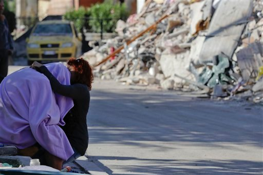 A man and woman comfort each other in front of a collapsed house, in Amatrice, Friday, Aug. 26, 2016.