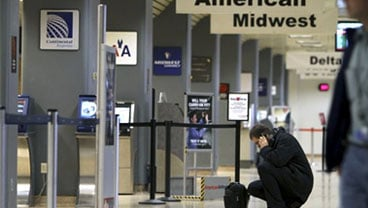 A passenger talks on his cell phone in the terminal at the Des Moines International Airport, Thursday, Nov. 19, 2009, in Des Moines, Iowa.  (AP Photo/Charlie Neibergall)