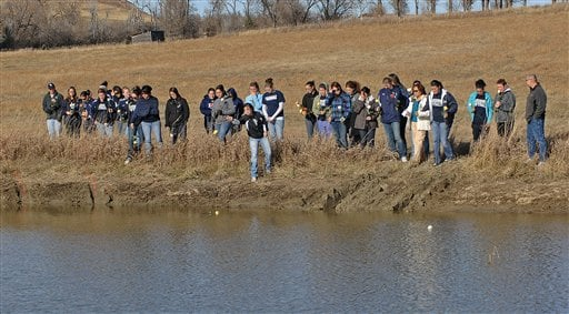 Members of the Dickinson State Softball team and victims' parents throw roses and softballs Wednesday Nov. 4, 2009 into the farm pond where three North Dakota college softball players were found dead inside their sunken sport utility vehicle in Dickinson,