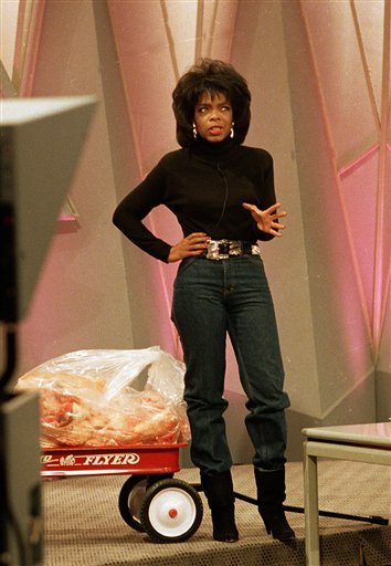 FILE - In this Tuesday, Nov. 16, 1988 file photo, television talk show host Oprah Winfrey shows off her new figure as she stands in front of 68 pounds of fat inside a toy wagon, in Chicago, Ill.