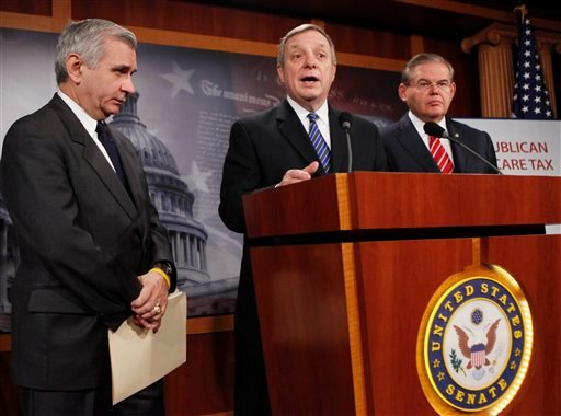 Senate Majority Whip Richard Durbin of Ill., center, accompanied by Sen. Jack Reed, D-R.I., left, and Sen. Robert Menendez, D-N.J., speaks during a health care reform news conference on Capitol Hill, Friday, Nov. 20, 2009.  (AP Photo/Manuel Balce Ceneta)