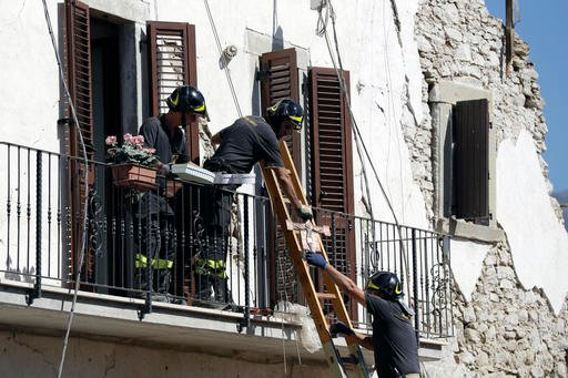 Firefighters recover a crucifix and personal belongings from a damaged house in the village of Rio, central Italy, Sunday, Aug. 28, 2016. Bulldozers with huge claws pulled down dangerously overhanging ledges Sunday in Italy's quake-devastated town of Amat
