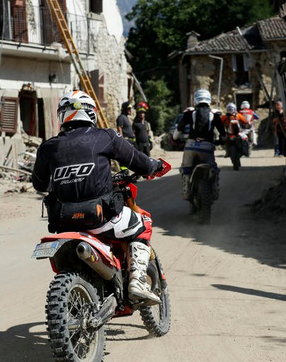 Volounteers on motorbikes drive through the town of Villa San Lorenzo a Flaviano, central Italy, as they bring goods to minor villages, Sunday, Aug. 28, 2016. Bulldozers with huge claws pulled down dangerously overhanging ledges Sunday in Italy's quake-de