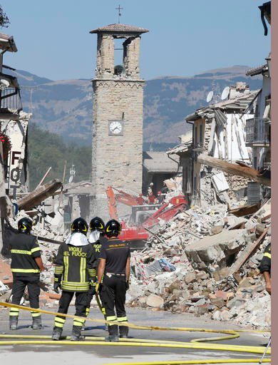 Firefighters stand by rubbles in Amatrice, central Italy, Sunday, Aug. 28, 2016 where a 6.1 earthquake struck just after 3:30 a.m., Wednesday. Bulldozers with huge claws pulled down dangerously overhanging ledges Sunday in Italy's quake-devastated town of