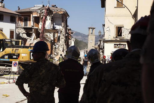 Firefighters work in Amatrice, central Italy, Sunday, Aug. 28, 2016. Bulldozers with huge claws pulled down dangerously overhanging ledges Sunday in Italy's quake-devastated town of Amatrice as investigators worked to figure out if negligence or fraud in