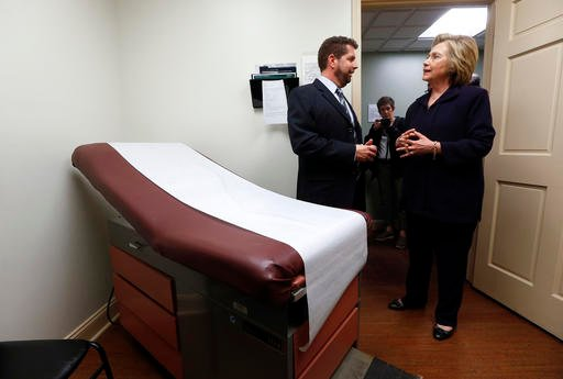 In this May 2, 2016 file photo, Democratic presidential candidate Hillary Clinton listens to Dr. Christopher Beckett, CEO of Williamson Health and Wellness Center during a tour an exam room of the facility in Williamson, W.Va. With the hourglass running o