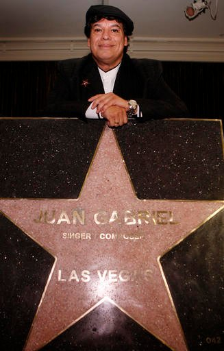In this Dec. 17, 2009, file photo, Juan Gabriel poses with his star which will be included in the Las Vegas Walk of Stars at the Mirage hotel & casino in Las Vegas. Representatives of Juan Gabriel have reported Sunday, Aug. 28, 2016, that he has died. Ju