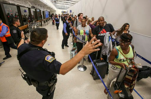 Police officers stand guard as passengers wait in line at Terminal 7 in Los Angeles International Airport, Sunday, Aug. 28, 2016. (AP Photo/Ringo H.W. Chiu)