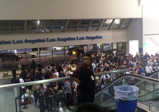 A crowd of people wait in Terminal 1 where passengers were being rescreened by security at Los Angeles International Airport after reports that a gunman opened fire Aug. 28, 2016. (Bari Ross via AP)