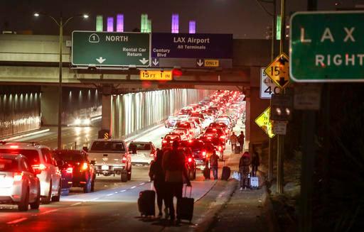 Passengers pull their luggage and walk toward Los Angeles International Airport, Sunday, Aug. 28, 2016. (AP Photo/Ringo H.W. Chiu)