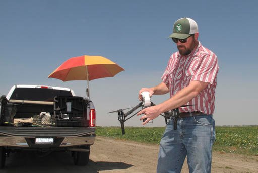 In this photo taken July 25, 2016, Danny Royer, vice president of technology at Bowles Farming Co., prepares to pilot a drone over a tomato field near Los Banos, Calif. (AP Photo/Scott Smith)