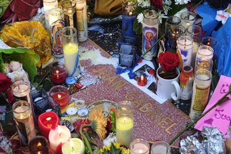 Flowers and candles surround the Hollywood star of Mexican superstar Juan Gabriel, in the Hollywood section of Los Angeles on Monday, Aug. 29, 2016. Gabriel a songwriter and singer who was an icon in the Latin music world, died Sunday at his home in Calif