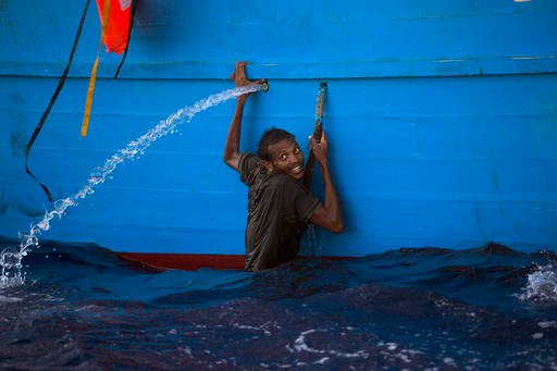 A man holds himself on the side of a boat after jumping into the sea from a crowded wooden boat during a rescue operation at the Mediterranean sea, about 13 miles north of Sabratha, Libya, Monday, Aug. 29, 2016.