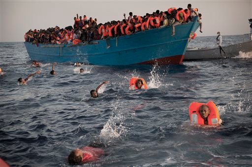 Migrants, most of them from Eritrea, jump into the water from a crowded wooden boat as they are helped by members of an NGO during a rescue operation at the Mediterranean sea, north of Sabratha, Libya, Monday, Aug. 29, 2016.