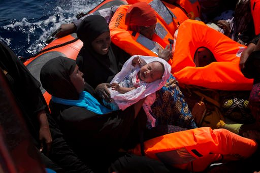 Migrant women from Nigeria, one of them holding a baby, are rescued by emergency teams from a dinghy as they were sailing at the Mediterranean sea toward the Italian coasts, about 17 miles north of Sabratha, Libya, Sunday, Aug. 28, 2016.