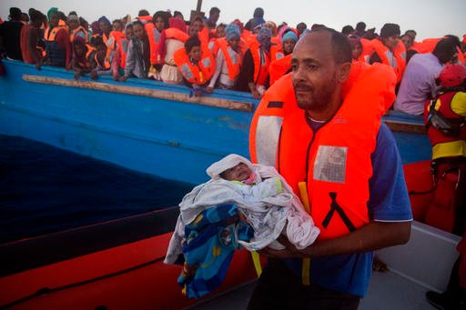 A man carries his five days old son after been rescued from a crowded wooden vessel as they were fleeing Libya, during a rescue operation in the Mediterranean sea, about 13 miles north of Sabratha, Libya, Monday, Aug. 29, 2016.