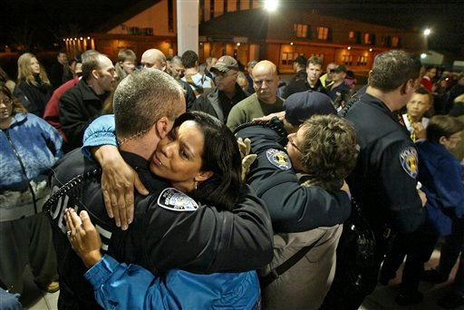 Black Diamond Police officer Brian Lynch, left, gets a hug from Lakewood resident Roberta Ladd as others in the crowd hug and share kind words with Police officers after a candlelight vigil at the Champions Centre, Sunday, Nov. 29, 2009, in Tacoma, Wash.