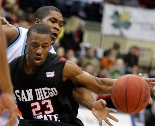 San Diego's Brandon Johnson, back, reaches around San Diego State's D.J. Gay to knock away the ball and resulting in a turnover during the first half of a NCAA college basketball game Wednesday Dec. 2, 2009 in San Diego. (AP Photo/Lenny Ignelzi)