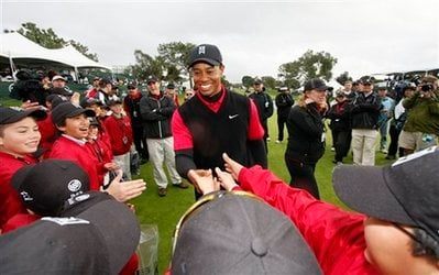 FILE - This is a Jan. 27, 2008, file photo showing Tiger Woods being congratulated by children from his Tiger Woods Learning Center, after his eight shot victory at the Buick Invitational golf tournament, in San Diego.