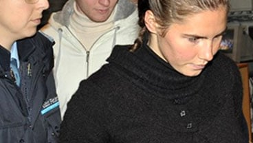 U.S. murder suspect Amanda Knox, right, is accompanied by a police penitentiary officer as Italian murder suspect Raffaele Sollecito is seen behind her as they arrives for a hearing at the Perugia court, Italy, Tuesday, Dec.1, 2009.(AP Photo/Stefano Med)