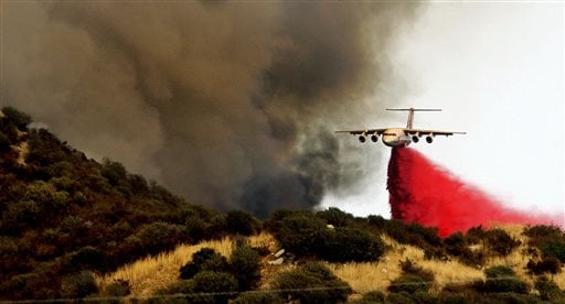 A jet tanker dumps retardant on the hillside above homes to block the southern movement of a wildfire.
