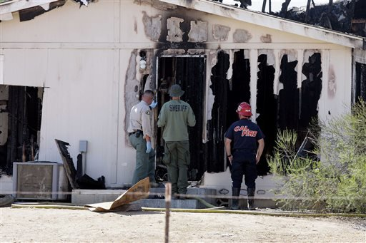 Arson and homicide investigators work on a house fire at a board-and-care facility after human remains were discovered.