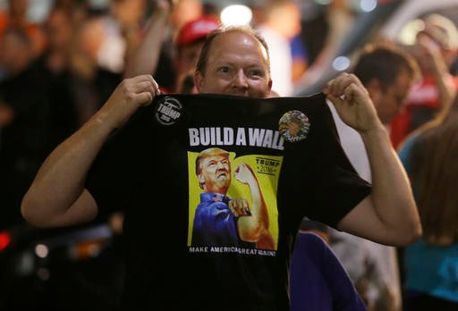 """A supporter of Republican presidential candidate Donald Trump holds up his shirt, which bears the Trump slogan """"Build a Wall,"""" following a rally for Trump."""