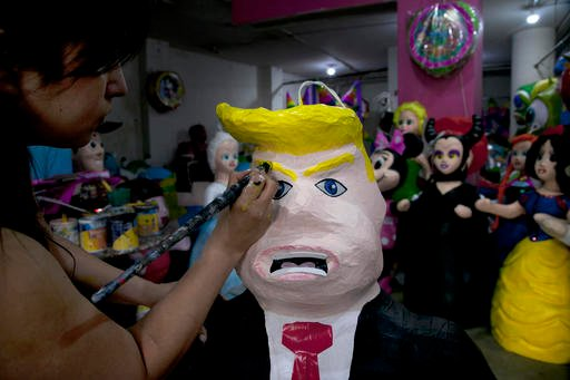 """In this Friday, July 10, 2015 file photo, Alicia Lopez Fernandez paints a pinata depicting Donald Trump at her family's store """"Pinatas Mena Banbolinos"""" in Mexico City."""