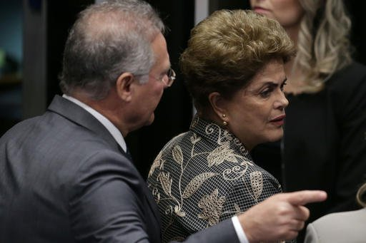 Brazil's Senate leader Renan Calheiros points to an exit as suspended President Dilma Rousseff looks to leave Senate chambers.