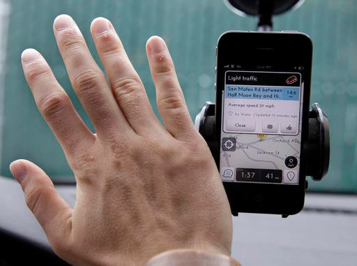 In this March 15, 2012, file photo, Ben Gleitzman waves his hand over a traffic and navigation app called Waze on his Apple iPhone in a Menlo Park, Calif., parking lot during a demonstration showing traffic conditions on the display. Google is set to expa