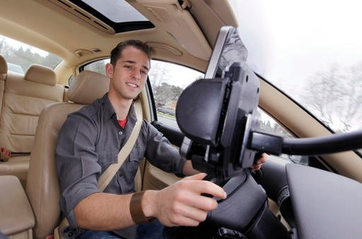 In this March 15, 2012 file photo, Ben Gleitzman uses a traffic and navigation app called Waze as he drives to work in Menlo Park, Calif. Google is set to expand a San Francisco carpooling program that could morph into a showdown with its one-time ally, t