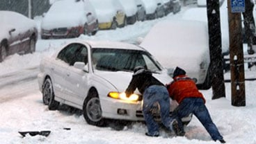 A motorist is pushed back onto an Albany, N.Y., street, as the area gets its first winter storm of the season on Wednesday, Dec. 9, 2009. (AP Photo/Mike Groll)