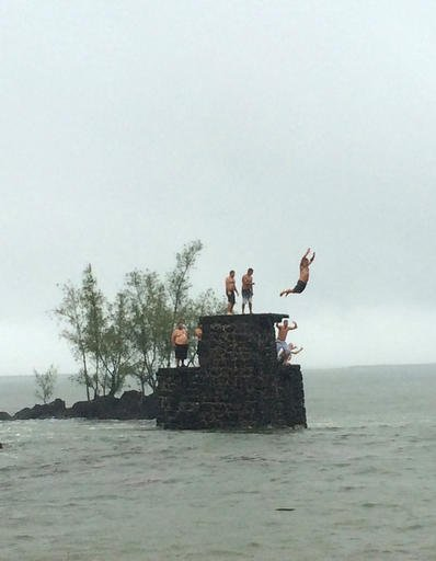 People jump into Hilo Bay in Hilo, Hawaii, as Topical Storm Madeline drops rain on Hawaii's Big Island, Wednesday, Aug. 31, 2016. Forecasters downgraded Madeline from a hurricane to a tropical storm as it veered past Hawaii's Big Island, but officials rei