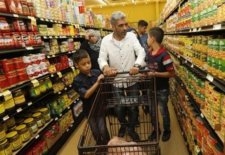 Days after participating in a ceremony in Jordan to mark the United States hitting its target of taking in 10,000 Syrian refugees, the former construction worker and his family buy roasted chicken, milk and fruit for their new home outside San Diego. (AP