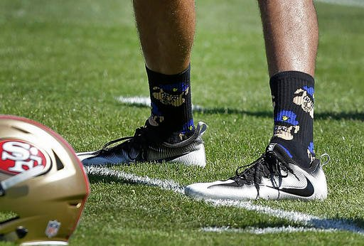 In this Aug. 10, 2016, file photo, San Francisco 49ers quarterback Colin Kaepernick wears socks depicting police officers as pigs during NFL football training camp at Kezar Stadium in San Francisco.
