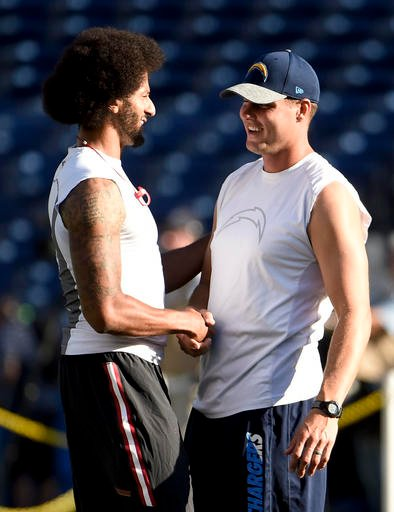 San Francisco 49ers quarterback Colin Kaepernick, left, talks with San Diego Chargers quarterback Philip Rivers during warm-ups for an NFL preseason football game Thursday, Sept. 1, 2016, in San Diego. (AP Photo/Denis Poroy)