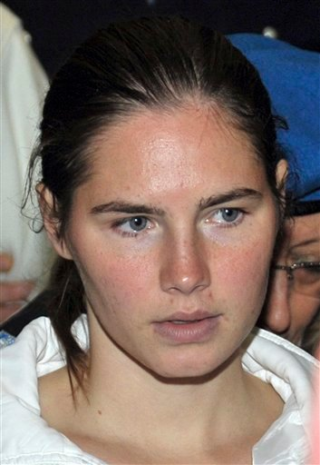 "FILE - Amanda Knox is escorted by an Italian penitentiary police officer at the end of a hearing in Perugia's court, Italy, in this Nov. 28, 2009 file photo. Amanda Knox tells The Associated Press Sunday Dec. 13, 2009 in her jail cell that she is ""scared"""