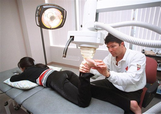 FILE - This Dec. 16, 1999, photo shows Dr. Anthony Galea treating a patient with shock wave therapy at the Institute of Sports Medicine in Toronto.