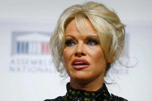 Pamela Anderson delivers her speech during a news conference at the French National Assembly.