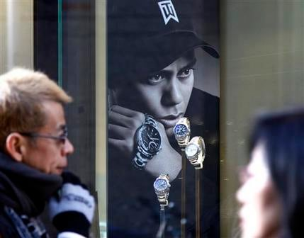 In this Tuesday, Dec. 15, 2009 file photo, people walk by a Swiss watch shop displaying watches along with U.S. golfer Tiger Woods' portrait in Tokyo. (AP Photo/Koji Sasahara)