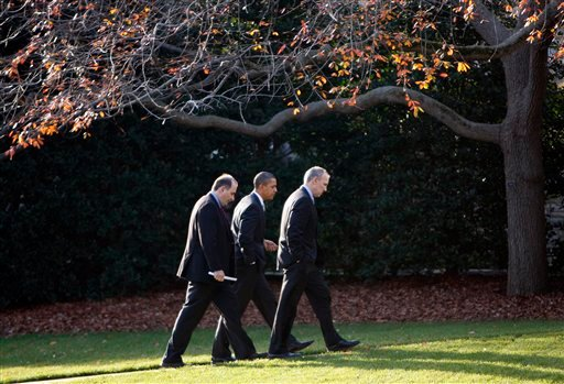 President Barack Obama, center, walks with senior adviser David Axelrod, left, and Legislative Affairs director Phil Schiliro, right, to the Oval Office of the White House after a trip Capitol Hill in Washington, Sunday, Dec. 6, 2009, to attend a Senate D