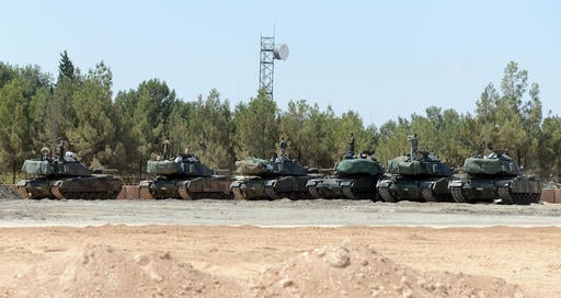 "Turkish tanks stationed near the Syrian border, in Karkamis, Turkey, Saturday, Sept. 3, 2016. Turkey's state-run news agency says Turkish tanks have entered Syria's Cobanbey district northeast of Aleppo in a ""new phase"" of the Euphrates Shield operation."