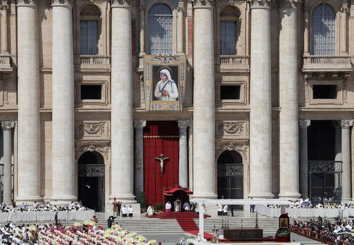 A tapestry depicting Mother Teresa hangs from the balcony of St. Peter's Basilica as Pope Francis, standing at bottom, celebrates a a Canonization Mass at the Vatican, Sunday, Sept. 4, 2016. Francis has declared Mother Teresa a saint, honoring the tiny nu