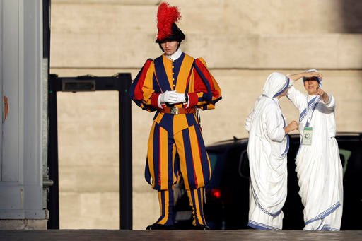 Nuns of Mother Teresa's Missionaries of Charity stand near a Swiss guard prior to the start of a mass celebrated by Pope Francis where Mother Teresa will be canonized in St. Peter's Square, at the Vatican, Sunday, Sept. 4, 2016. (AP Photo/Gregorio Borgia)