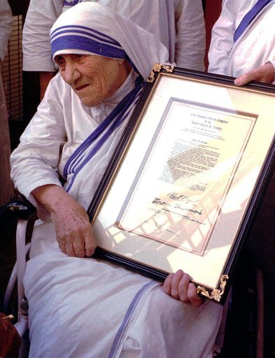In this Saturday, Nov. 16, 1996 file photo, Mother Teresa holds the resolutions of honorary American citizenship after they were presented to her by American Ambassador to India Frank G. Wisner at the Missionaries of Charity in KolKata, formerly known as