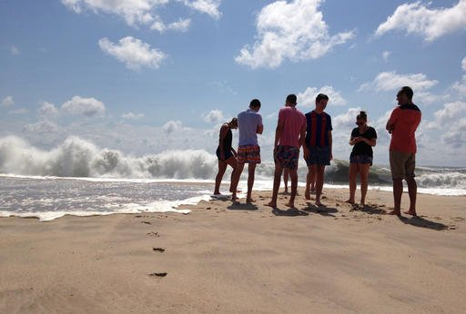 Beachgoers stand at the edge of the water, Sunday, Sept. 4, 2016, in Bridgehampton, N.Y., on the southeastern shore of Long Island, where the effects of storm system Hermine could be seen in the rough surf and a ban on swimming. Hermine spun away from the