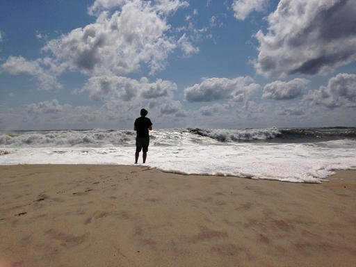 A beachgoer stands at the edge of the water, Sunday, Sept. 4, 2016, in Bridgehampton, N.Y., on the southeastern shore of Long Island, where the effects of storm system Hermine could be seen in the rough surf and a ban on swimming. Hermine spun away from t