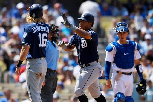 San Diego Padres' Yangervis Solarte, center, is congratulated by Travis Jankowski, left, after hitting a two-run home run as Los Angeles Dodgers catcher Austin Barnes watches during the third inning of a baseball game, Sunday, Sept. 4, 2016, in Los Angele