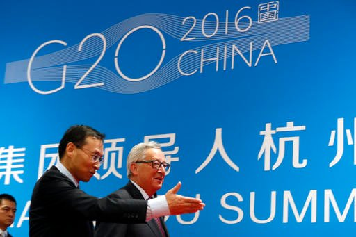 European Commission President Jean-Claude Juncker, right, is shown the way by a Chinese official as he arrives at the G20 Summit in Hangzhou in eastern China's Zhejiang province, Sunday, Sept. 4, 2016. European Union leaders have called for China to take