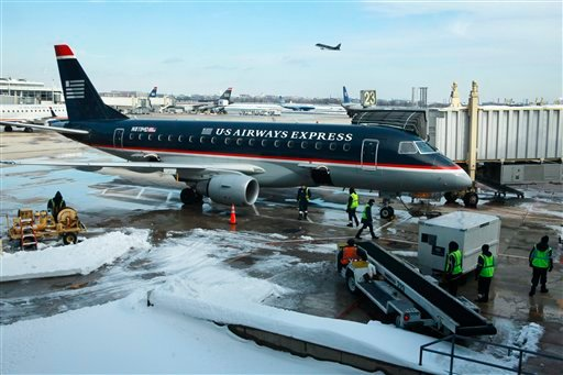 A U.S. Airways Express plane is prepared on the tarmac at Reagan National Airport, after a massive snow storm shut down air travel over the weekend, in Washington, on Monday, Dec. 21, 2009. (AP Photo/Jacquelyn Martin)